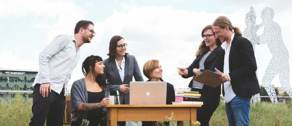 Eine Gruppe Menschen draußen vor der Spree in Berlin um einen Tisch mit Laptop. Gestatten: Unser Büro für Branding in Berlin.