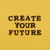 """Eine gelbe Fläche mit dem Text """"CREATE YOUR FUTURE"""" – hoffentlich kommst du mithilfe unserer Anleitung zur Visionsreise zu deinem Vision-Statement!"""